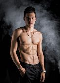 stock photo of single man  - Lean athletic shirtless young man standing on dark background with smoke around him - JPG