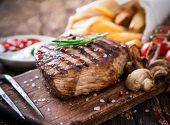 stock photo of bbq food  - Delicious beef steak on wooden table - JPG