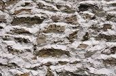 picture of gneiss  - Stone wall with white cement closeup in sunny day - JPG