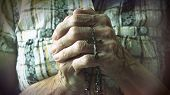 stock photo of crucifix  - Hands of an old woman holding a rosary or crucifix while praying to God the Creator and Savior daily Cristian devotional - JPG