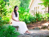 pic of biracial  - Beautiful biracial bride in white lace wedding dress sitting on bench outdoors smiling - JPG