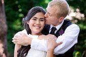 picture of biracial  - Caucasian groom lovingly kissing his biracial bride on cheek - JPG
