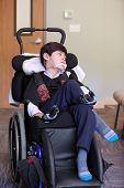 pic of biracial  - Handsome disabled eight year old biracial boy smiling and relaxing in wheelchair - JPG