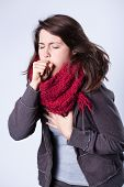 stock photo of cough  - Coughing girl in scarf having high fever - JPG