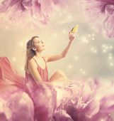 stock photo of surreal  - Beautiful young woman with a small butterfly on peony flower - JPG