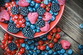 picture of berries  - Mix of fresh berries in a plate on rustic wooden background. Focus on the berries on the table ** Note: Shallow depth of field - JPG