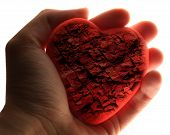 stock photo of broken heart  - Red broken heart in male hand in closeup - JPG