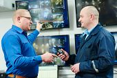 stock photo of security  - security executive chief discussing activity with worker in front of video monitoring surveillance security system - JPG