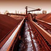 foto of sedimentation  - loading iron ore conveyor machine from the warehouse mining production - JPG