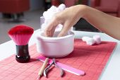 picture of nail salon  - hand dipped in a white bowl ready to a manicure treatment on a placemat on a table near a nail file a brush and a cuticule remover at a beauty salon - JPG