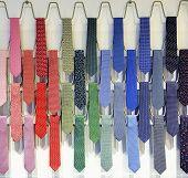 foto of chokers  - Rows of varicolored silk male business ties on a tie rack - JPG