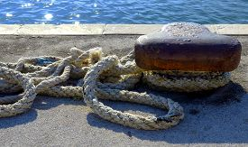 picture of safe haven  - Thick Rope Securely Tied around Bollard at the Harbor - JPG