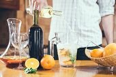 stock photo of sangria  - Man pouring white wine into a jar - JPG