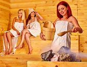 picture of sauna woman  - Women pouring water on rock in sauna - JPG