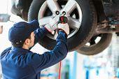 picture of car repair shop  - Mechanician changing car wheel in auto repair shop - JPG