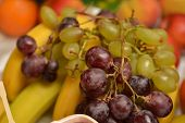 stock photo of fruit platter  - Fruit platter with banana and grapes with side light - JPG