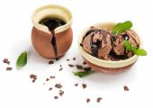 stock photo of chocolate-chip  - Chocolate ice cream in a brown ceramic bowl with mint chips chocolate topping and pitcher with chocolate sauce isolated on white background - JPG