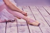 picture of ballet shoes  - Professional ballerina putting on her ballet shoes on the wooden floor on a pink background - JPG