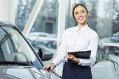 pic of showrooms  - Young pretty woman dealer in showroom standing near car  - JPG