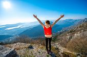 foto of vest  - Sport woman in red vest standing on the top of mountain - JPG