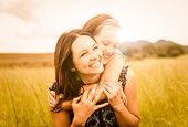 pic of hug  - Mother and child are hugging and having fun outdoor in nature - JPG