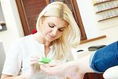 foto of toe nail  - Pedicure nail technician worker perfoming procedure for foot care in beauty salon - JPG