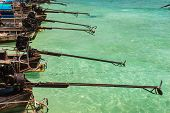 image of outboard engine  - a row of several long tail boats a traditional thai vessel - JPG