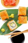 pic of soy sauce  - Maki Sushi with Salmon Crab Avocado and Cheese on Green Palm Leafs with Soy Sauce Ginger and Pair of Chopsticks isolated on white background - JPG