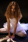 stock photo of daydreaming  - Portrait of daydreaming young ballet student sitting on floor in ballet costume - JPG