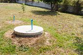 image of septic  - underground cement cylinder of lavatory cesspit in lawn yard - JPG