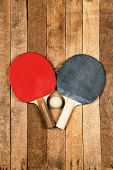 picture of ping pong  - Ping pong paddles and ball on wooden background - JPG