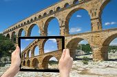stock photo of aqueduct  - In the bottom left of the photo are hands holding tablet whose screen contains photo of the Pont du Gard - JPG