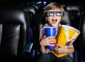image of watching movie  - Surprised boy holding snacks while watching 3D movie in cinema theater - JPG