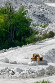 pic of bulldozer  - A heavy treaded bulldozer plow sits idle on the chalk white inclined road in a marble mine ready to begin working - JPG
