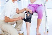 stock photo of medical examination  - Doctor examining her patients knee in medical office - JPG