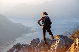 picture of big-girls  - Young traveler with backpack standing on the big stones on the mountain and observing locality - JPG