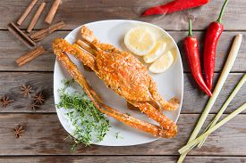 picture of cooked crab  - Top view cooked delicious hot and spicy sauce blue crab on white plate with ingredients - JPG