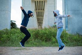 pic of respirator  - Two young people in the respirators jumping outdoors - JPG