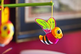 stock photo of jousting  - Little bee hanging above baby bed - JPG