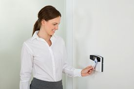 picture of insert  - Young Businesswoman Smiling While Inserting Keycard In Door Security System - JPG