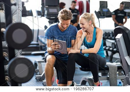 poster of Smiling personal trainer using digital tablet while talking to blonde woman at gym. Happy couple usi