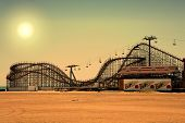 pic of amusement park rides  - old fashioned wooden rollercoaster at dusk fall - JPG
