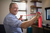 Smiling senior male patient pulling red resistance band at hospital poster