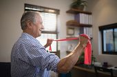 Side view of senior man pulling resistance band while standing in hospital ward poster