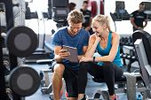Smiling personal trainer using digital tablet while talking to blonde woman at gym. Happy couple usi poster