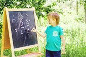 Cute Little Boy Writing Letters And Numbers At Blackboard In The Garden. poster