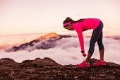 Trail runner woman tying running shoes laces getting ready to run on mountains nature in summer suns poster