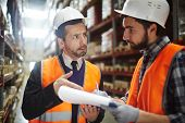 Portrait of warehouse worker talking to supervising manager while doing inventory control in entrepo poster