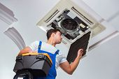 Worker repairing ceiling air conditioning unit poster
