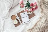 Wooden tray with tablet, coffee and spring flowers on clean white bedding. Good morning concept. poster